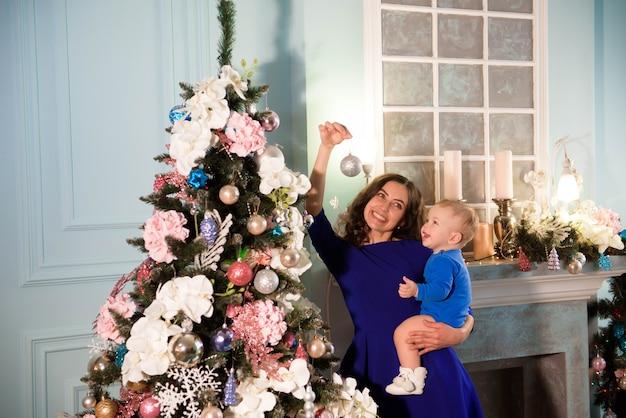 Ragazzo carino e sua madre che decorano l'albero di natale per le vacanze