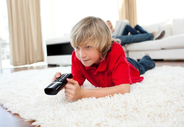 Ragazzo carino in possesso di un telecomando sdraiato sul pavimento