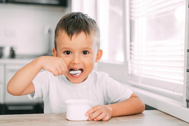 Ragazzo carino in cucina che mangia yogurt in vestiti leggeri da un contenitore di yogurt bianco, un posto per la pubblicità