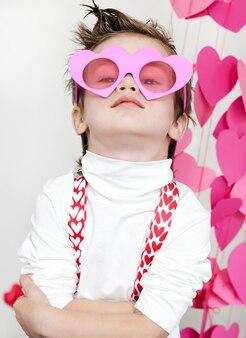 Ragazzo carino in occhiali a forma di cuore rosa