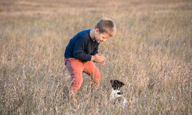 Ragazzo carino che gioca con il suo cane nel prato