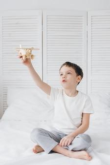 Ragazzo sveglio che gioca con l'aeroplano di legno che si siede sul letto