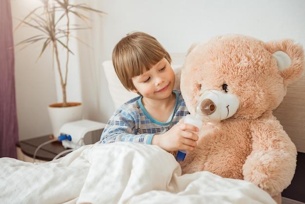 Il ragazzo carino mette una maschera per inalazione sul suo orsacchiotto preferito