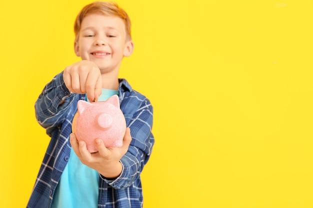 Ragazzo carino mettere soldi nel salvadanaio su sfondo colorato
