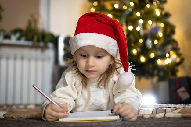 Il ragazzo sveglio in maglione rosso e cappello rosso della santa scrive una lettera a babbo natale