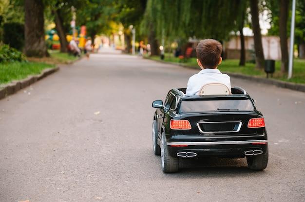 Ragazzo carino in sella a un'auto elettrica nera nel parco
