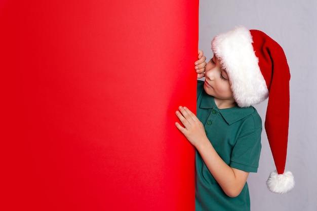 Il ragazzo sveglio in berretto di babbo natale guarda il manifesto rosso della carta di carta isolato sopra lo spazio di fondo di colore per testo. foto di alta qualità