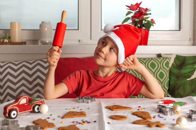 Un ragazzo carino con un cappello di babbo natale prepara il pan di zenzero al tavolo e tiene in mano un mattarello rosso