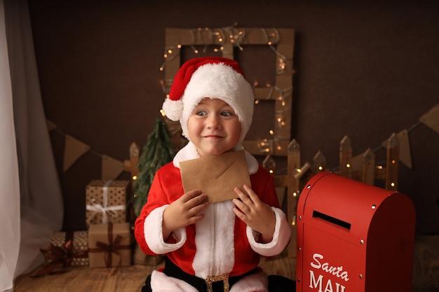 Ragazzo carino in costume da babbo natale invia una lettera a babbo natale