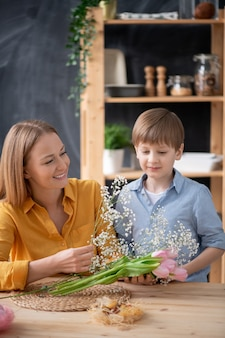 Ragazzo carino in camicia in piedi al tavolo e aiutare la madre a organizzare bouquet di tulipani e respiro del bambino in cucina