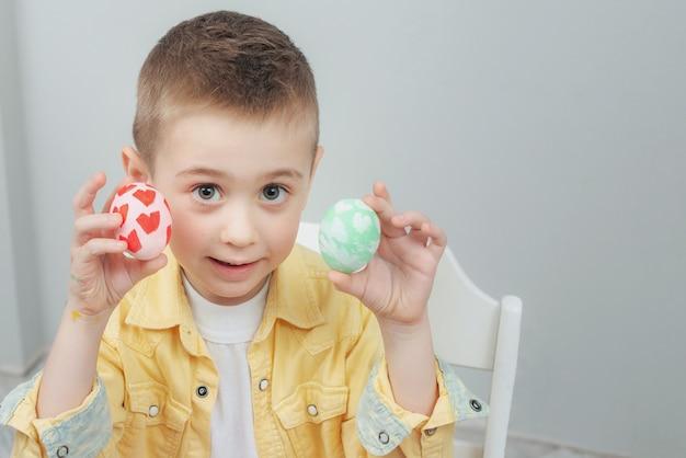 Ragazzo sveglio che mostra le uova di pasqua dipinte