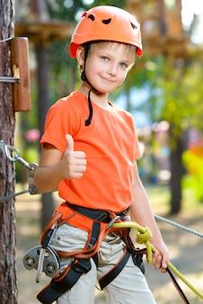 Il ragazzo sveglio mostra il pollice su con l'attrezzatura rampicante in un parco di avventura