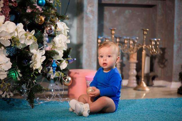 Ragazzo carino seduto sul tappeto vicino all'albero di natale