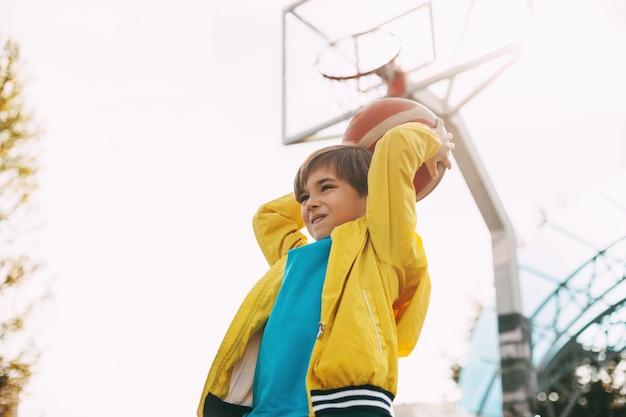 Un ragazzo carino in uniforme sportiva tiene un pallone da basket tra le mani e si prepara a lanciare, sport