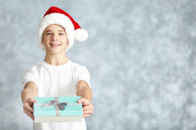 Ragazzo carino con confezione regalo blu su superficie grigia