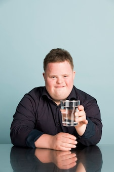 Ragazzo carino con sindrome di down con in mano un bicchiere d'acqua