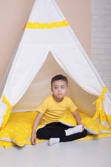 Ragazzo carino con sindrome di down seduto in una capanna gialla