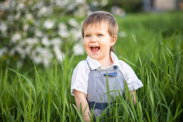Un ragazzo carino con gli occhi azzurri espressivi in una tuta alla moda sorride divertente e si nasconde nell'erba verde alta