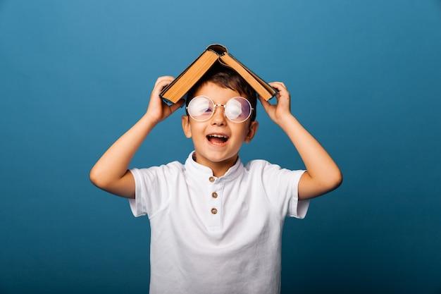 Un simpatico ragazzo con gli occhiali tiene un libro in testa, su sfondo blu. ragazzo con un libro mostra la lingua. scolaro.