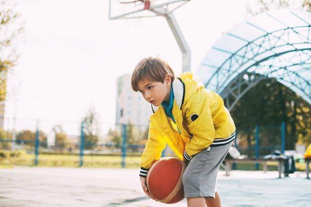 Un ragazzo carino con una giacca sportiva gialla lancia un pallone da basket. un bambino gioca a basket.
