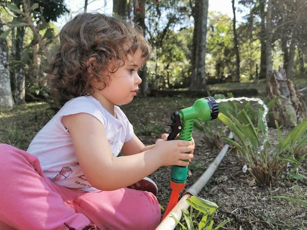Bambina brasiliana sveglia divertendosi a giocare con il tubo dell'acqua in giardino.