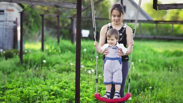 Il simpatico fratello e la sorella maggiore cavalcano su un'altalena luminosa in una calda giornata primaverile sullo sfondo di un verde giardino fiorito