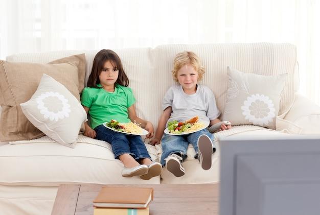 Carino fratello e sorella cenando sul divano
