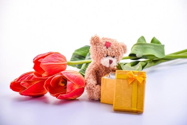 Simpatico orsacchiotto marrone, bouquet di tulipani rossi, confezione regalo, per san valentino, anniversario, primo piano