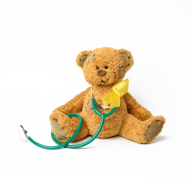 Simpatico orsacchiotto marrone con una toppa, un nastro giallo di seta a forma di cappio su bianco