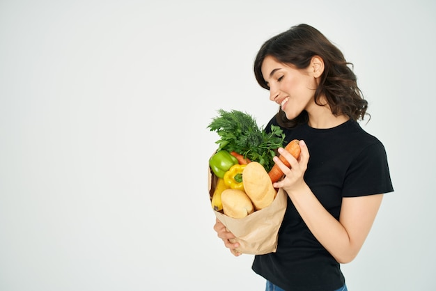 Bruna carina nel pacchetto maglietta nera con generi alimentari del supermercato