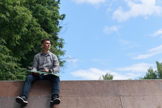 Ragazzo carino brunetta guardando al lato e tenendo lo skateboard seduto sullo scivolo di skateboard nel parco su sfondo blu cielo in una calda giornata estiva, copyspace