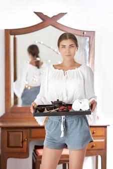 Una bruna carina è in piedi con un vassoio in mano con un caffè e biscotti, asciugamani, decorazioni e una teiera cinese. buona colazione la routine mattutina