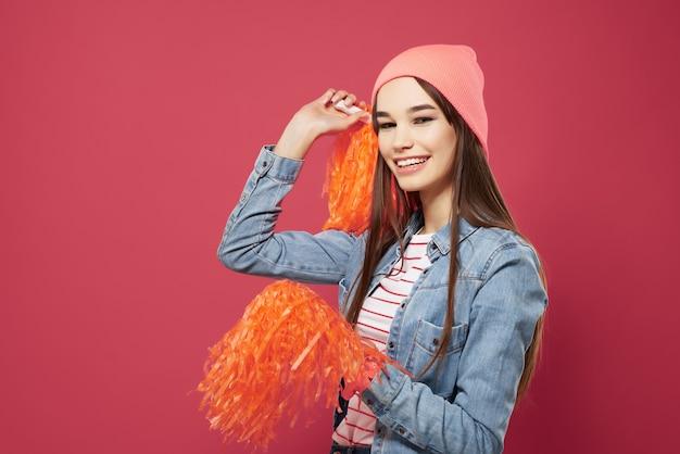 Brunetta carina che indossa un cappello rosa cheerleading dance vittoria