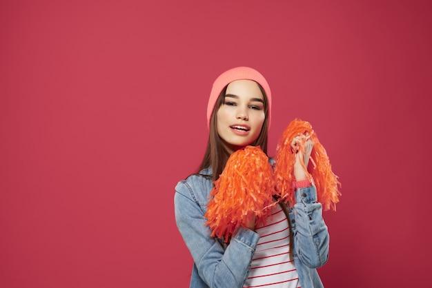 Brunetta carina che indossa un cappello rosa cheerleader danza vittoria