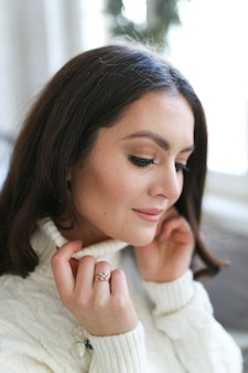Carina donna bruna in un caldo abito bianco sta riposando sul letto vicino alla finestra decorato con una ghirlanda
