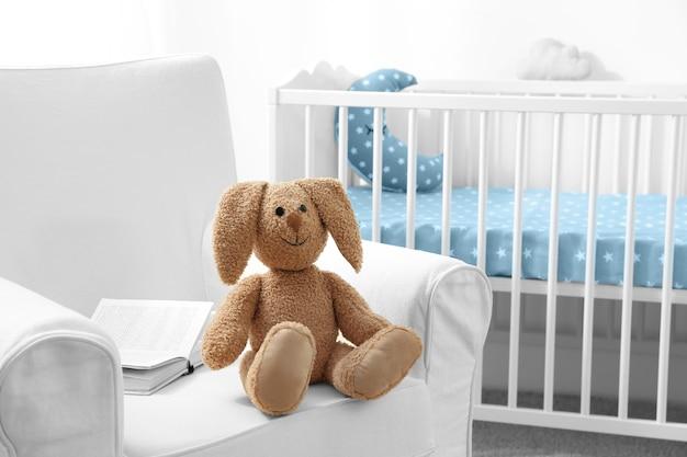 Giocattolo simpatico coniglietto sulla poltrona nella stanza del bambino