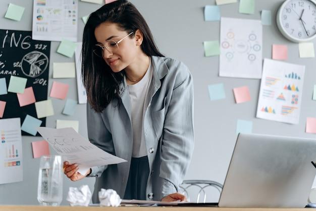 Carina ragazza d'affari con gli occhiali lavora in ufficio, studia attentamente i documenti