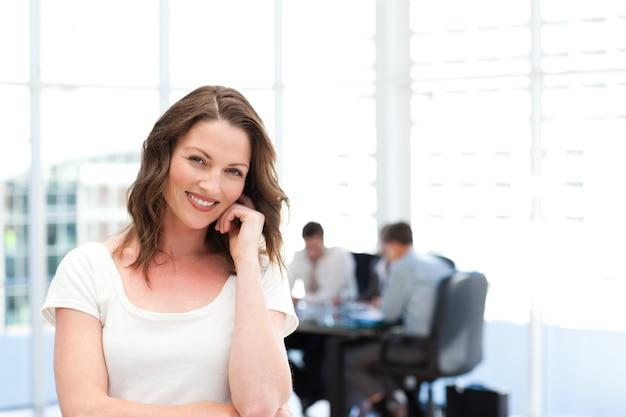 Donna di affari sveglia che sta davanti alla sua squadra mentre lavorando