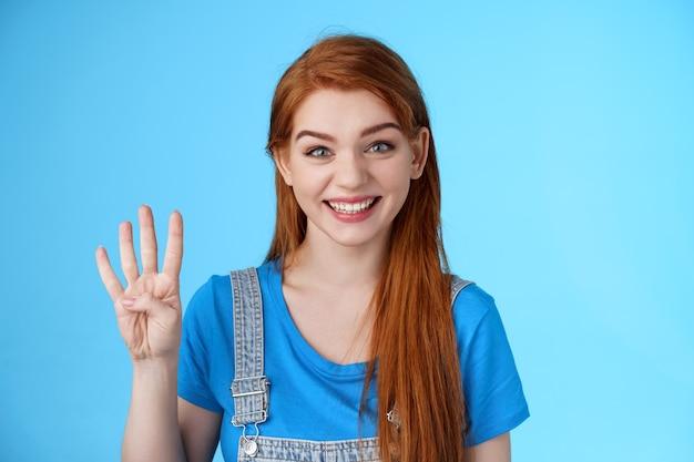 Carino spensierato shopping femminile rossa, mostra quattro dita, numero quarto sorridente fortunato ottimista, espressione positiva divertita, fai ordine tavolo prenotazione per gli amici, stand sfondo blu
