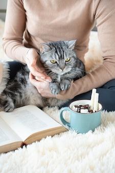 Simpatico gatto in mani femminili. tazza di gustoso cacao e libro sulla morbida coperta. ambiente familiare accogliente. il testo nel libro non è riconoscibile.