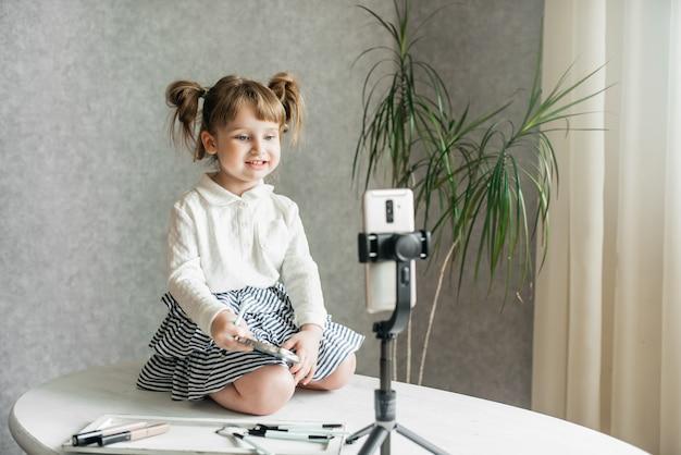 Video vlogger della neonata caucasica sveglia, telefono su un treppiede.