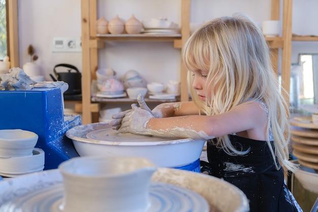 Bambina bionda caucasica carina che modella l'argilla sul tornio da vasaio