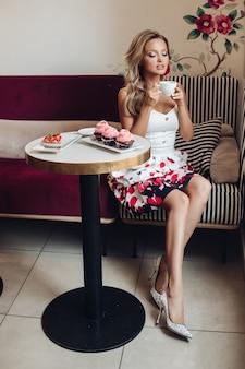 Una graziosa femmina caucasica con lunghi capelli biondi ondulati beve caffè e mangia deliziosi cupcakes rosa durante la colazione bra