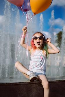 Carina ragazza caucasica con i capelli tinti colorati che indossano gli occhiali da sole delle mamme che tengono i palloncini seduti vicino a fo