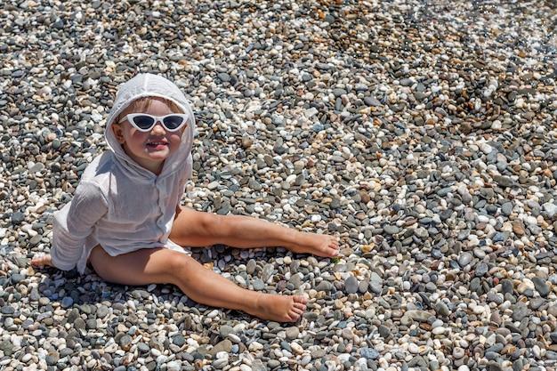 Carino bambino caucasico felice con un sorriso si siede sulla spiaggia con gli occhiali e guarda la telecamera. copia spazio per il testo