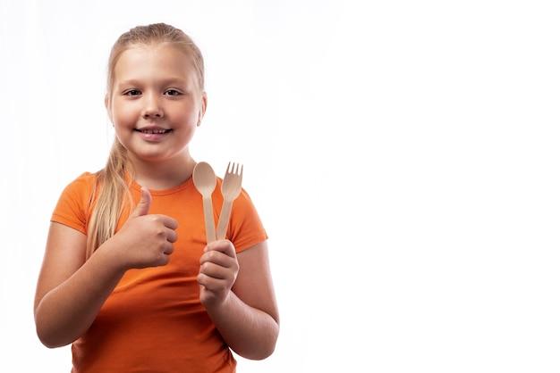 Bambina caucasica carina che tiene in mano posate di bambù e mostra i pollici in su su uno sfondo bianco. posate in legno di bambù. rifiuti zero concetto, riciclaggio.