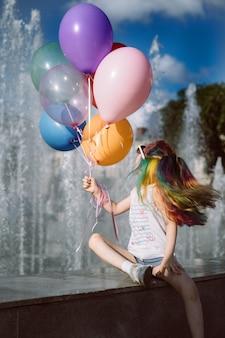 Carina ragazza sorridente caucasica con capelli tinti colorati che indossano occhiali da sole per le mamme che tengono i palloncini seduti