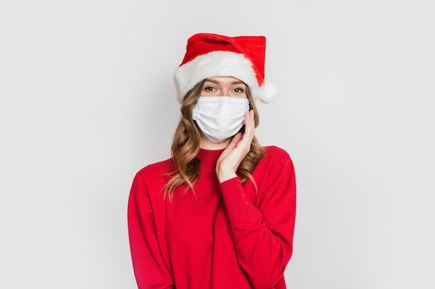 Ragazza carina studentessa caucasica che indossa una maschera medica e un maglione rosso cappello santa tiene la mano vicino al viso isolato su sfondo bianco studio