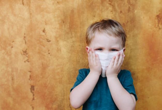 Bambino caucasico sveglio del bambino con la mascherina protettiva medica sul suo fronte durante la pandemia globale del virus corovavirus covid-19