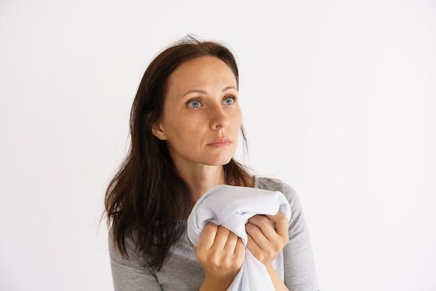 Una graziosa donna caucasica con in mano una camicia profumata bianca e pulita su una superficie chiara